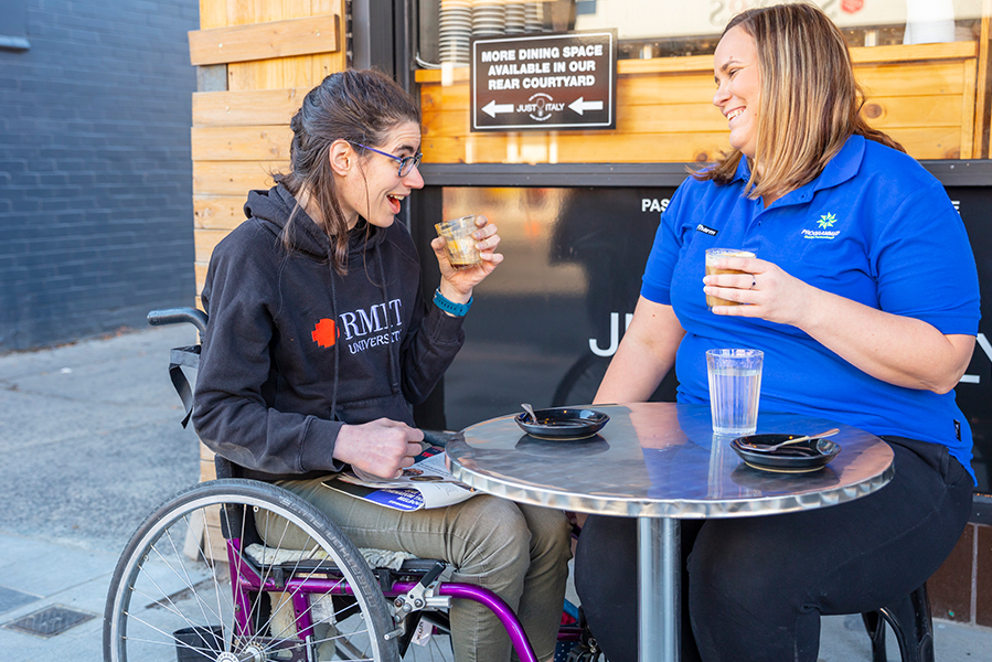 Person with disability having coffee with support worker